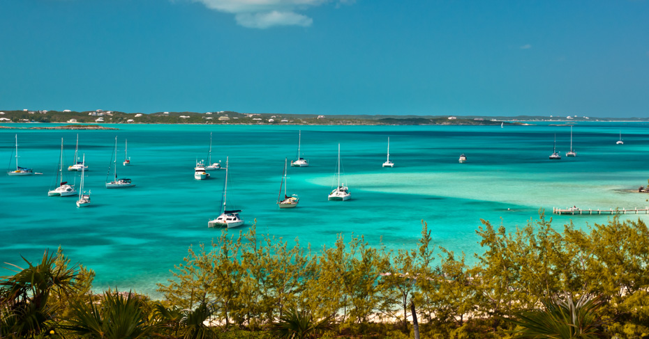 Places to visit in the Bahamas Exumas with many sailboats and power boats anchored in crystal clear turquoise waters of the bahamas. Disocver where to go in the Bahamas with the Bahamas Air Tour Guide book