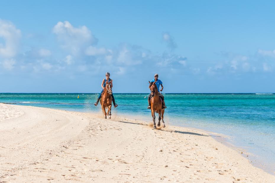 Couple riding on horseback along the sea on the Bahamas Sea