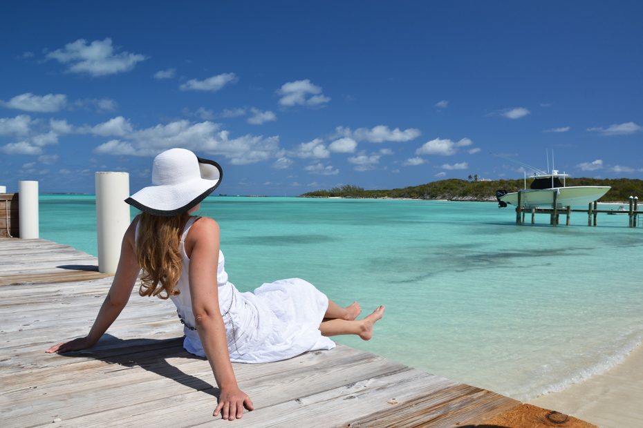 Girl on the wooden jetty looking to the ocean at Staniel Cay Exuma, Bahamas. Join the Staniel Cay Tours on any of the many Staniel Cay Day Trips from Florida