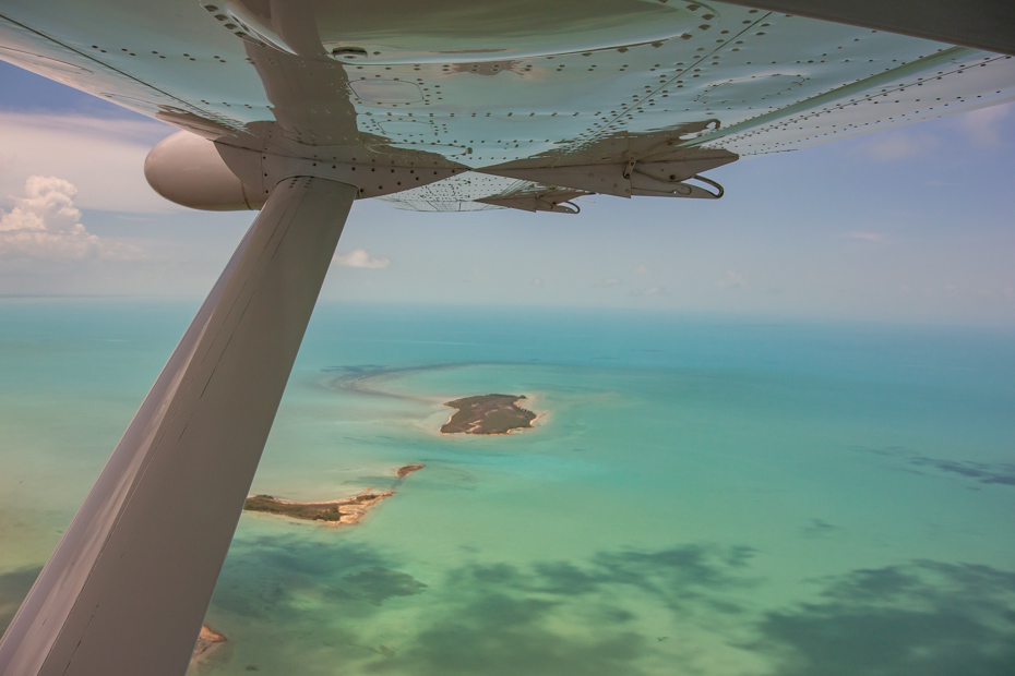 Aerial shot above the waters of the Bahamas. Bahamas air tours offers Florida to Bahamas flights from Miami above the excellent Exuma Bahamas scenery.