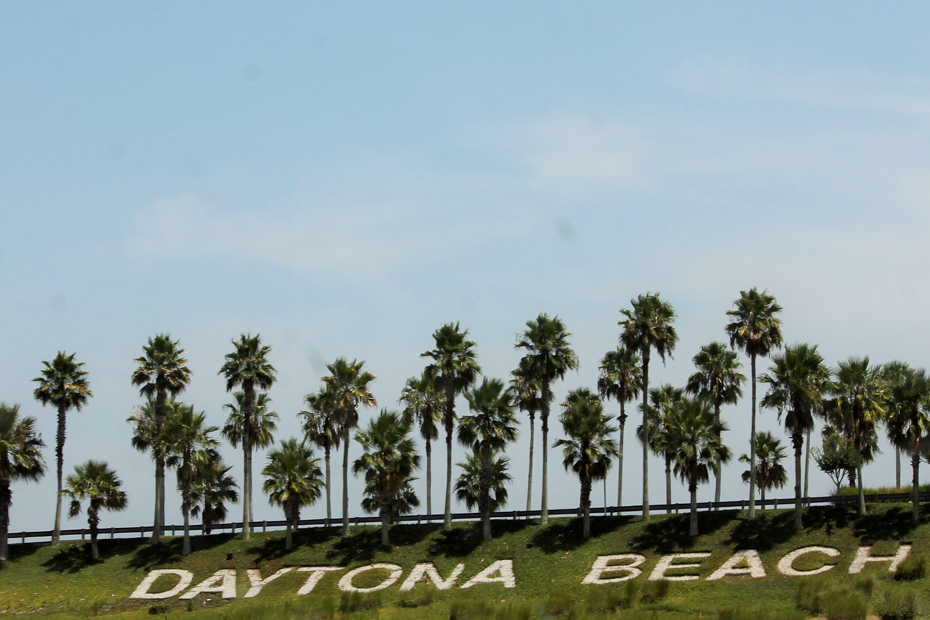 Daytona Beach sign surrounded by grass and palm trees. There are plenty of things to do in Daytona Beach Boardwalk. A Miami to Bahamas day trip is one of the top Florida attractions waiting to be explored with Bahamas Air Tours.